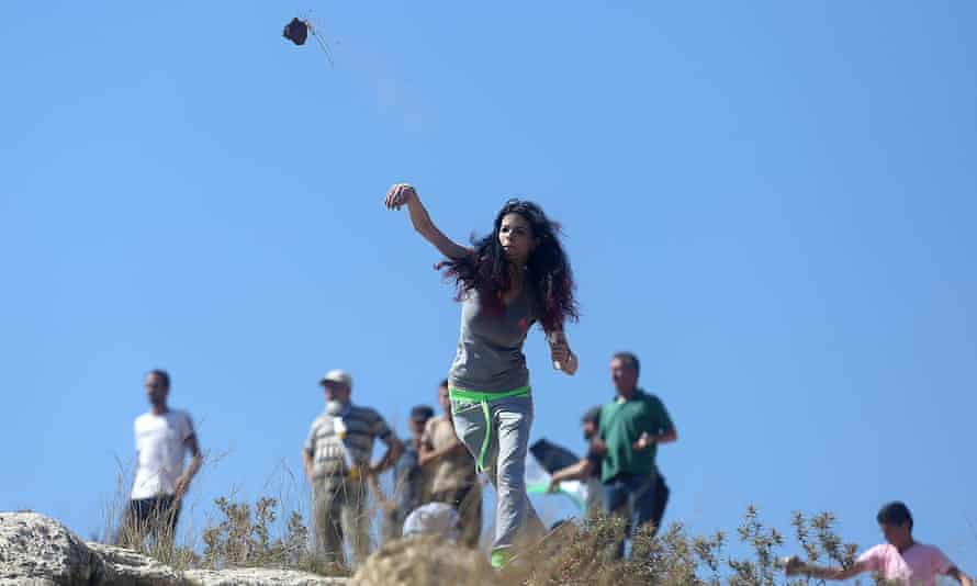 A Palestinian woman throws stones at Israeli soldiers following a protest against expropriation of Palestinian land by Israel in Nabi Saleh village, near Ramallah.