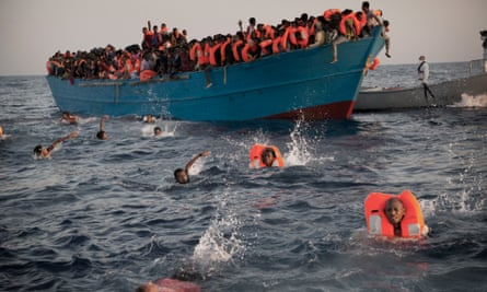 People leap into the water as they are helped by an NGO rescue operation in the Mediterranean near Libya