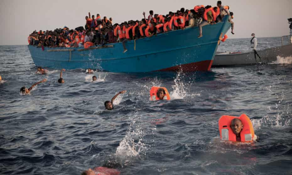 Migrants, many from Eritrea, jump into the water from a crowded wooden boat as they are helped by members of an NGO during a rescue operation in the Mediterranean sea about 13 miles north of Sabratha in Libya, August 2016.