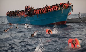 Eritrean migrants jump into the water during a rescue operation near the Libyan coast in August 2016.