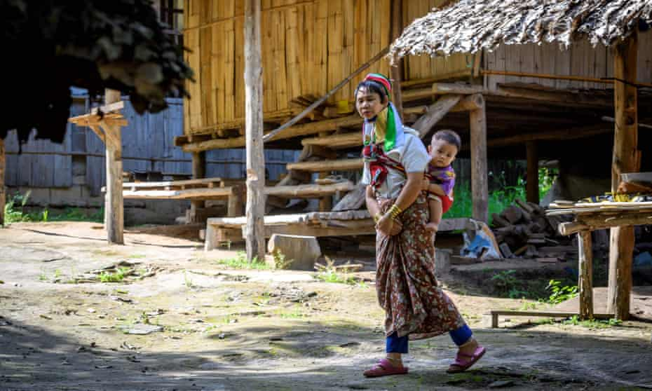 A long neck Karen woman carries a baby on her back in Baan Tong Luang hill tribes village