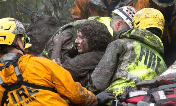 Firefighters carrying a woman rescued from a collapsed house after a mudslide in Montecito