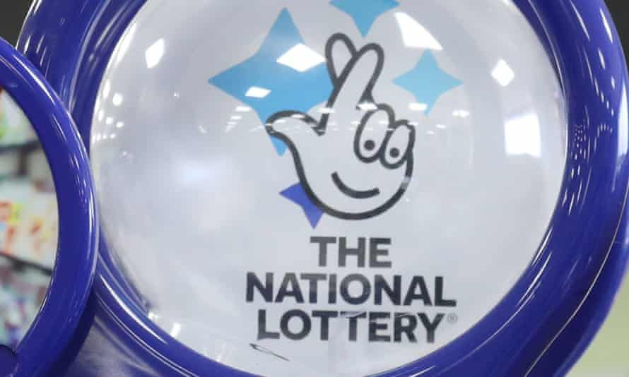 Close up of a national lottery ticket holder with its logo of a 'face' made up of a hand with crossed fingers