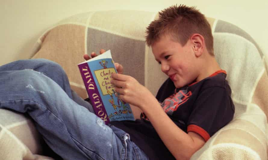 A young reader engrossed in Roald Dahl's Charlie and the Chocolate Factory.