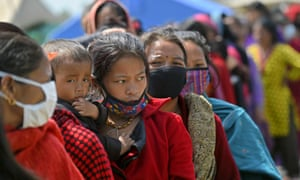 A Nepalese woman and her child line up with others to receive a daily stipend of food from the Nepalese army at a camp in Kathmandu on May 1, 2015