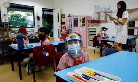 Anak-anak yang memakai masker dan pelindung wajah menghadiri kelas prasekolah di Singapura, yang merupakan salah satu negara dengan angka kelahiran terendah di dunia.