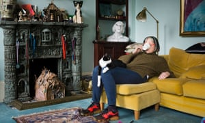 Philippa Perry reclining on her sofa, a mug over her face as she drinks from it, and Kevin the cat on her lap, his paw hanging down over her knee