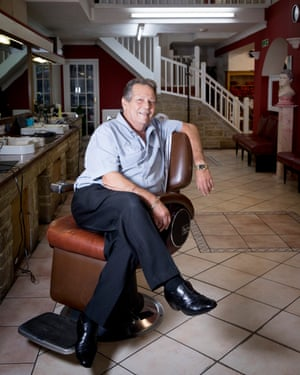 Hairdresser Giovanni Gomma sits on a barber chair inside his Aldershot salon