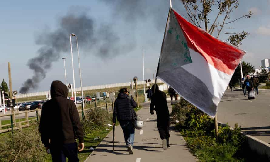 Migrants leave the refugee camp in Calais last October(one carrying the Sudanese flag).