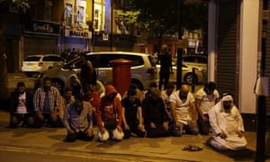 Muslims pray on a pavement in the Finsbury Park area of north London after a vehichle hit pedestrians