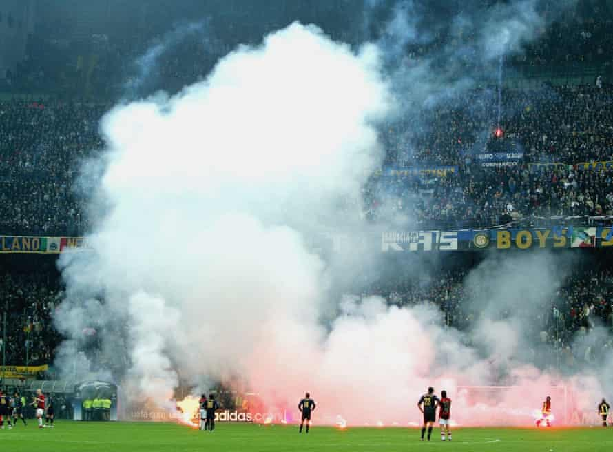Fans shower the San Siro pitch with flares.
