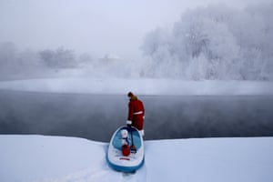 Paddle boarder Yevgeny Popov wearing a Santa Claus costume prepares to surf on a confluent of the Ob River.