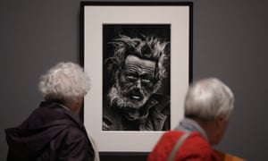 Visitors look at a 1970 photograph of a homeless Irishman in east London by Don McCullin.