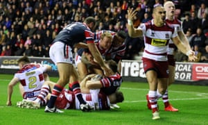 Thomas Leuluai of Wigan Warriors protests to the referee as the Sydney Roosters celebrates their side's second try scored by Brett Morris.