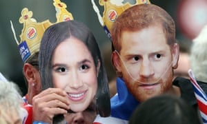 People holding masks of the faces of Britain's Prince Harry and his wife Meghan, Duchess of Sussex