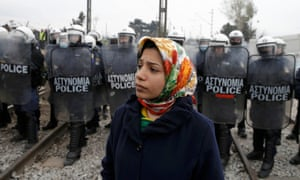A refugee stands in front of a line of Greek police near the village of Idomeni.