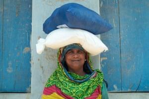 A woman in Nepal bears food packs on her head