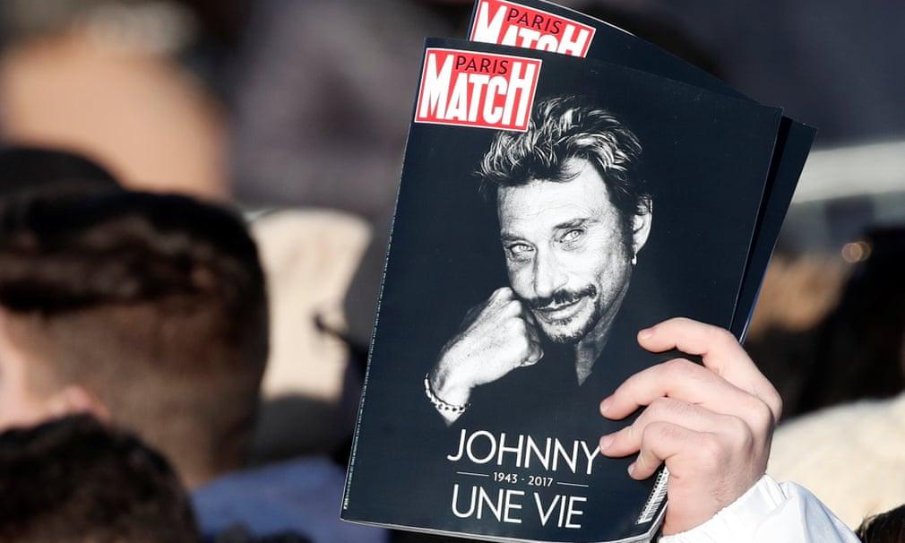 Fans on the Champs-Élysées hold copies on Paris Match
