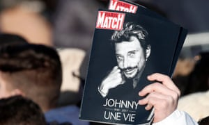 Fans on the Champs-Élysées hold copies on Paris Match
