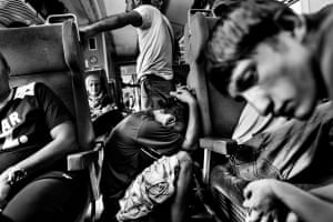 Refugees, mostly coming from Syria and Afghanistan, rest on the train while traveling through Macedonia.
