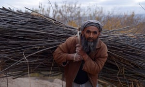 An Afghan man on the outskirts of Mazar-i- Sharif carries firewood for use as cooking fuel.
