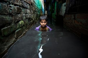 Winner of the Built Environment category: Raju Ghosh with 'Struggle'Ghosh's photograph shows a small boy struggling through an alleyway flooded with monsoon rain in a West Bengal slum. Inadequate infrastructure presents constant challenge for the slum dwellers.