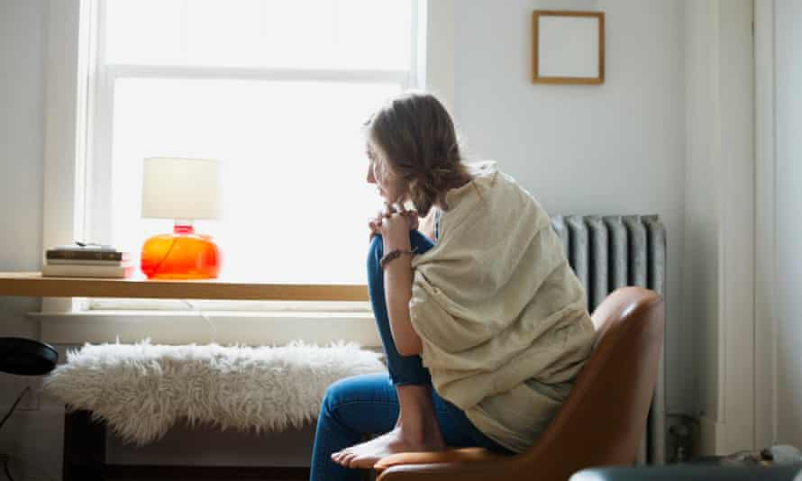 Pensive woman looking out living room