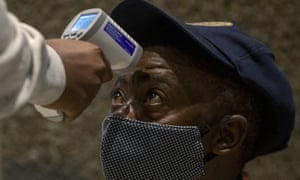 A police officer has his temperature taken as part of a mass screening campaign in Johannesburg, South Africa