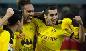 Pierre-Emerick Aubameyang celebrates after his goal with Shinji Kagawa and Henrikh Mkhitaryan. He was booked for removing his shirt to reveal a message aimed at Schalke fans.