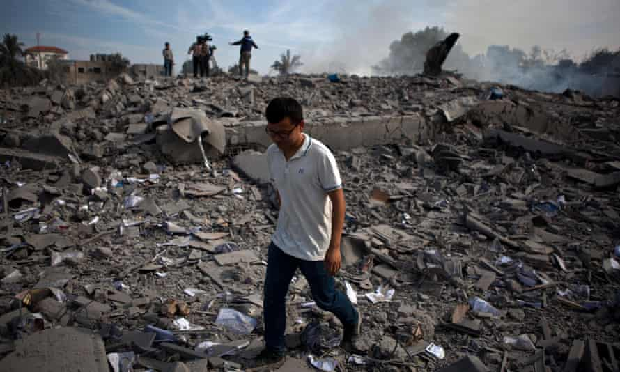Chen Xu walks through the ruins of a building in the Gaza Strip after it was levelled by an Israeli airstrike in November 2012.