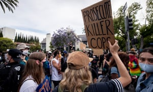 A protester holds a placard reading 'Prosecute Killer Cops' in front of Los Angeles mayor Eric Garcetti's house.