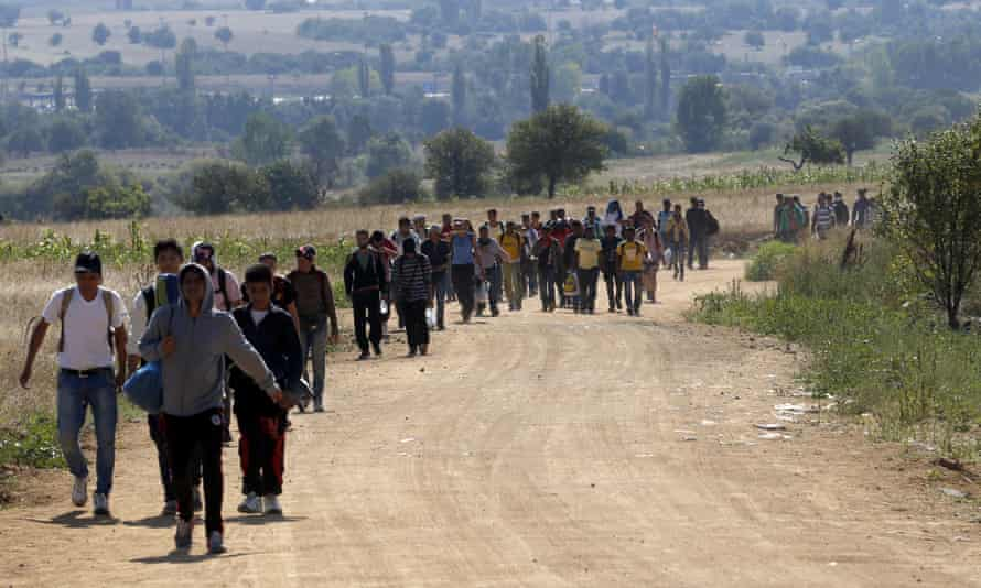 Migrants walk from the Macedonian border into Serbia