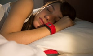 A woman in bed wearing a Pillow Talk wristband