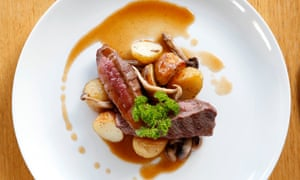 Roast venison on a round white plate with potatoes and gravy