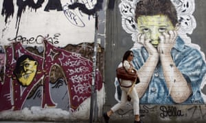 A pedestrian walks past a graffiti in central Athens, April 26, 2015. REUTERS/Kostas Tsironis
