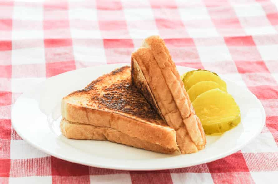 A toasted cheese sandwich with pickles
