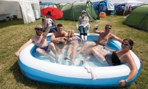 revellers toast the warm weather in a paddling pool at Glastonbury festival
