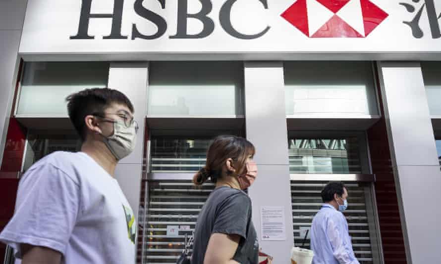 shoppers pass an HK branch of HSBC