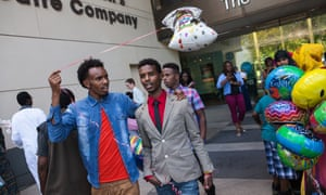 Two friends walk out of the Minneapolis Children's Theatre Company after a high school graduation ceremony. Young Somali men are especially affected by stereotypes of Islamic radicalization.