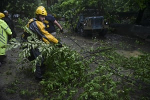 Joshua Alicea, rescue staff member from the Municipal Emergency Management Agency, removes a fallen tree in the Matelnillo community of Fajardo, Puerto Rico, while searching for citizens in distress.