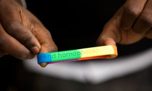 A protester holds a bracelet with the message 'end homophobia'
