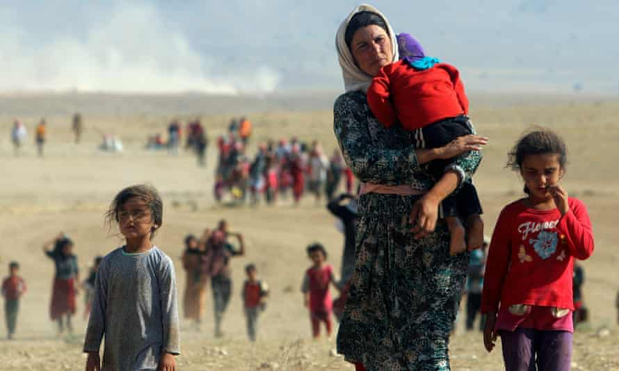 Displaced people from the minority Yazidi sect flee violence from forces loyal to the Islamic State and walk toward the Syrian border in 2014.