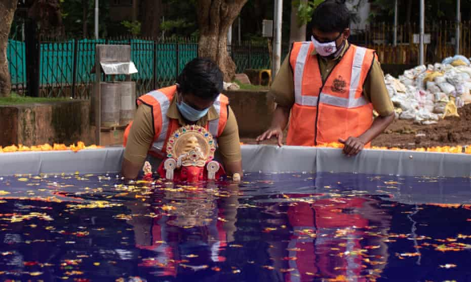 Brihanmumbai Municipal Corporation workers immerse an idol in a decorated artificial pond installed at August Kranti Maidan in Mumbai.