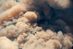 A firefighting airplane flies away from a pyrocumulus ash plume after making a retardant drop as firefighters continue to battle the Apple fire.