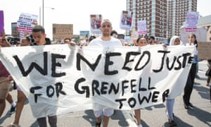 Protesters hold signs calling for justice for the victims of the Grenfell Tower fire.