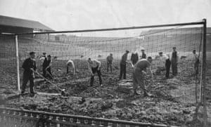 Volunteers clear debris from Millwall's pitch after an air raid