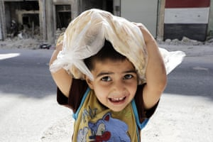A boy carries a bag filled with bread in the Kallaseh district of Aleppo city