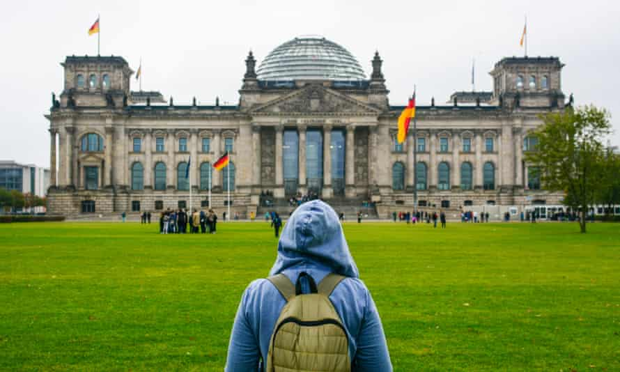Young woman with backpack looking at Bundestag building in Berlin.