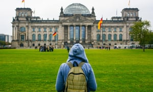 Young woman with backpack looking at Bundestag building in Berlin