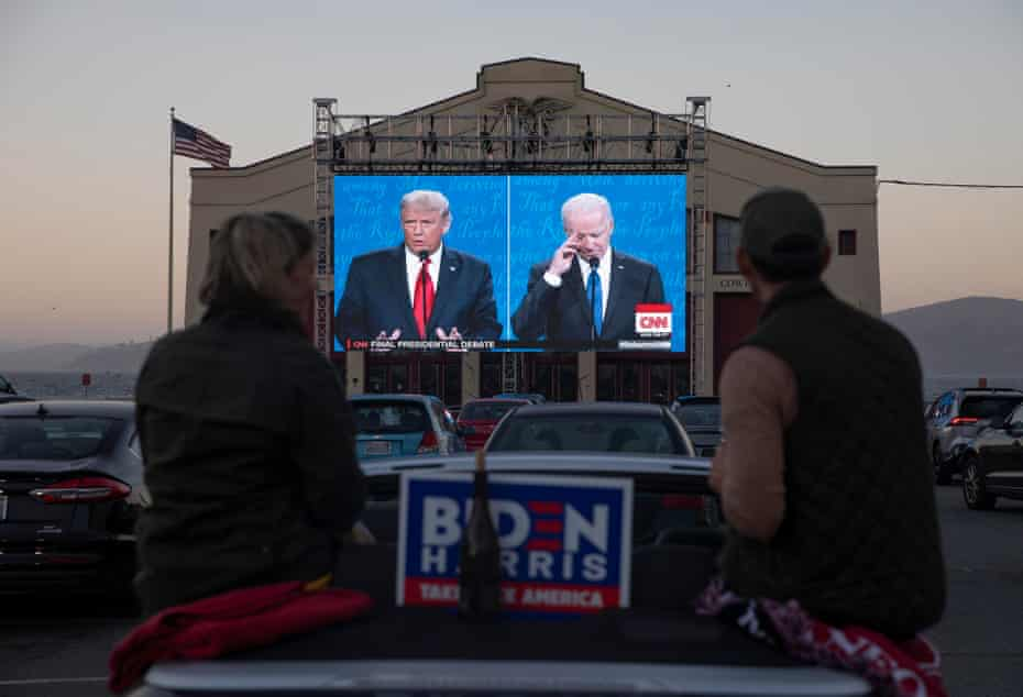 People watch the final presidential debate between Donald Trump and Joe Biden outside Cowell Theater on 22 October in San Francisco, California.